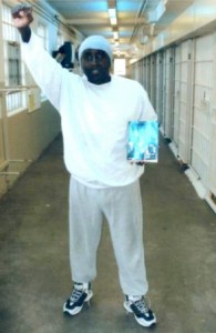 Kenny Zulu Whitmore holding the autobiography of Angola Three member Robert Hillary King
