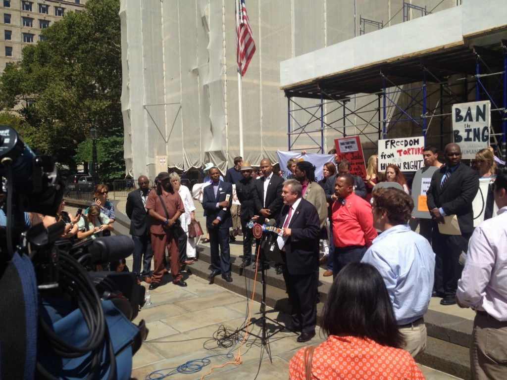 City Council Member Daniel Dromm speaks, surrounded by advocates, on the step of City Hall.