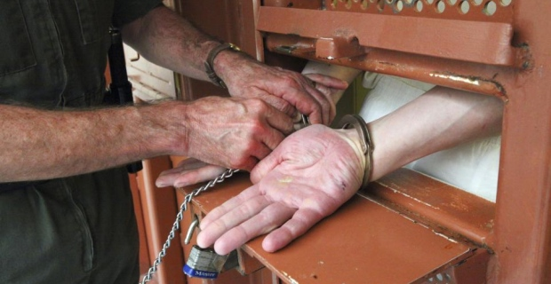A prisoner is shackled prior to his cell door bring opened (Credits: The New York Times / Jim Wilson)